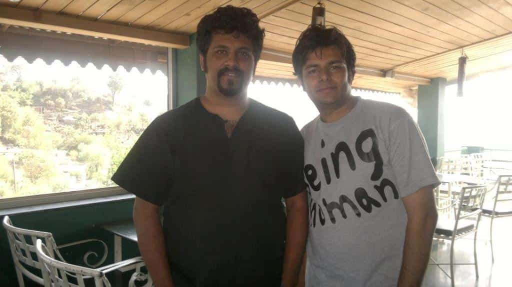Raghu Dixit is posing with a guest at Hangout Rooftop Bar and Lounge